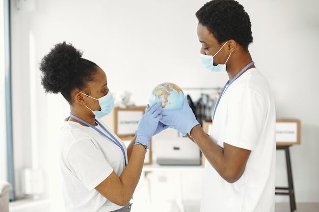 手に地球儀。保護マスクと手袋。男と女のアフリカ人。