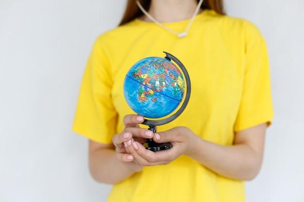 黄色のtシャツのクローズアップで女の子の手に地球儀