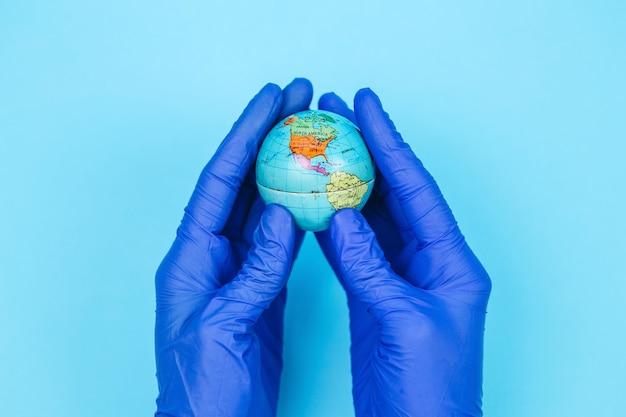 医者の手の中のグローブ。惑星の住民はコロナウイルスと戦っています。世界的なパンデミックcovid19。医療マスクのグローブ。