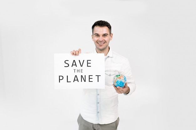 若い男と紙のポスターの手の中のグローブは、白い背景で隔離の惑星のテキストを保存します。地球の概念を保存します。
