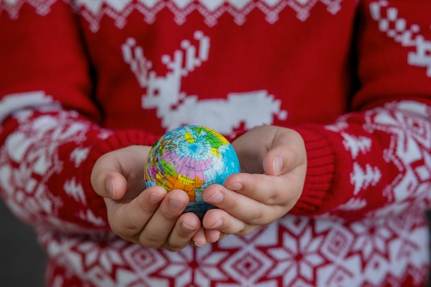 Globe in kids hands in christmas sweater. christmas minimalism concept. high quality photo