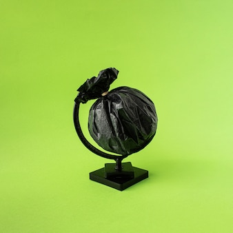 Globe made of black garbage bag. planet earth in plastic. green background. minimal concept.