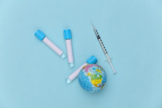 글로브, 파란색 배경에 주사기와 의료 테스트 튜브. 글로벌 백신.
