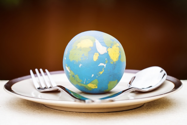 Globe model placed on plate with fork spoon for serve menu in famous hotels. international cuisine