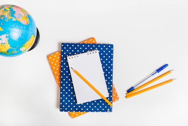 Глобус рядом с ноутбуками и письменными принадлежностями