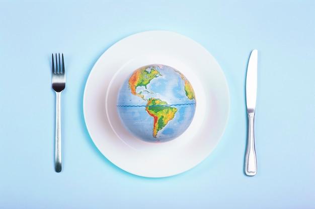 青の背景に食べ物のためのプレート上の地球儀。権力、経済、政治、グローバリズム、飢餓、貧困、そして世界の食糧の概念。