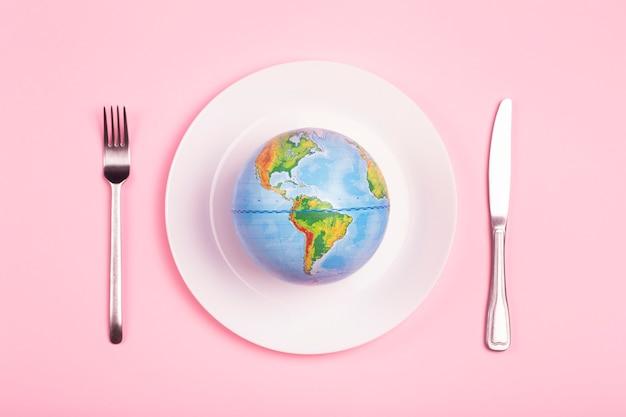 ピンクの背景に食べ物のためのプレート上の地球儀。権力、経済、政治、グローバリズム、飢餓、貧困、そして世界の食糧の概念。