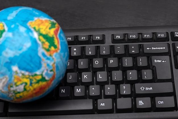 Глобус на клавиатуре компьютера. концепция глобального компьютерного бизнеса. интернет-путешествия.