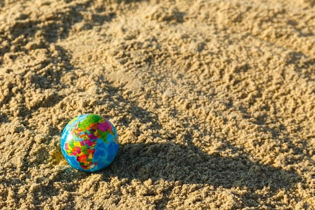 Globe of the planet  earth on a sandy beach close up.