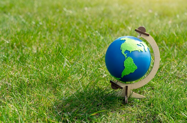 Globe of the planet earth standing on green grass in sunny day on spring or summer, eco symbol, green map on blue globe on lawn in the garden with copy space