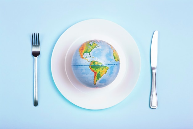 Globe on a plate for food on a blue background. power, economy, politics, globalism, hunger, poverty and world food concept.