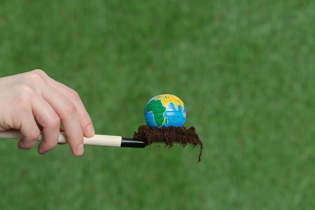 The globe on a shovel with earth of grass. earth day. planet earth.