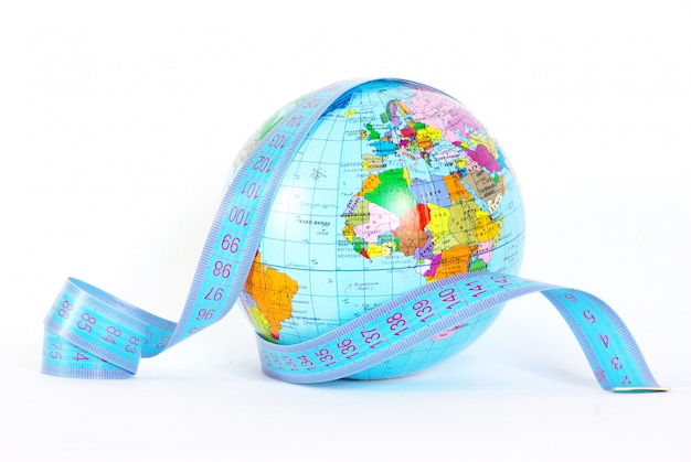 Globe with measuring tape on white