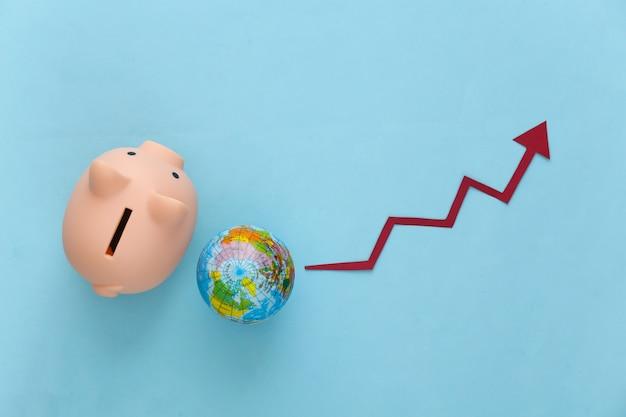 Globe with piggy bank  growth arrow tending up on a blue