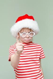 Мрачный злой мальчик в новогодней шапке угрожает пальцем