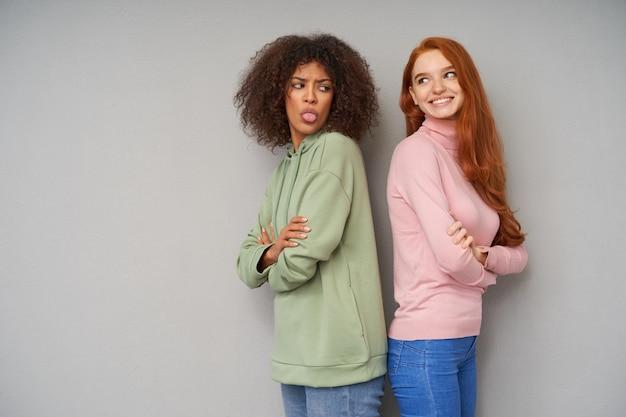 灰色の壁に隔離された、長いセクシーな髪のかなりポジティブな若い女性に舌を見せている緑のパーカーの暗い魅力的な茶色の髪の暗い肌の女性