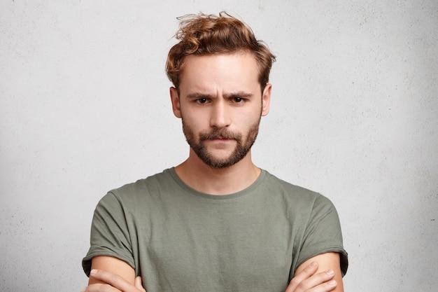 Хмурый бородатый парень недоволен результатами конкурса, скрестив руки,