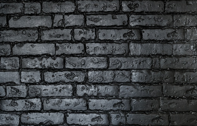 Gloomy, black brick wall of dark stone texture