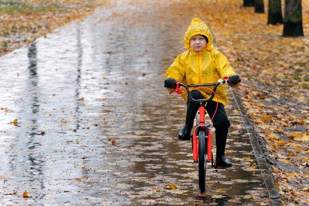 Мрачный мальчик в желтом плаще едет на велосипеде по мокрой аллее под дождем. осенний день
