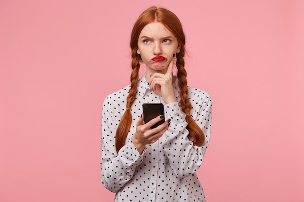Gloomy brooding red-haired girl without enthusiasm looking in the upper left corner trying to think of what to write in a message to her friend holding the phone in her hands, on pink wall
