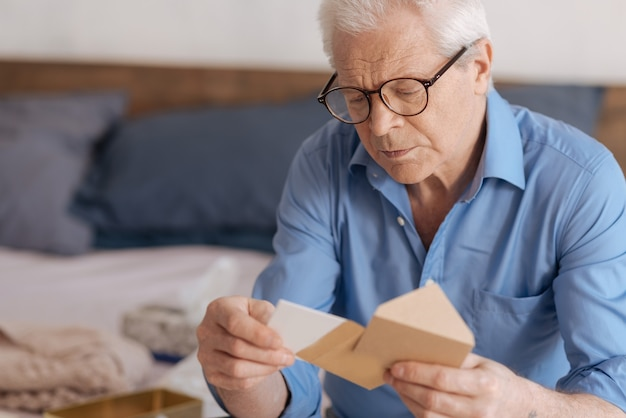 Gloomy cheerless aged man holding an envelope and taking out a note while intending to read it