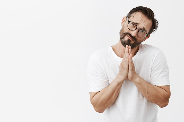 Gloomy and clingy bearded mature man with glasses posing
