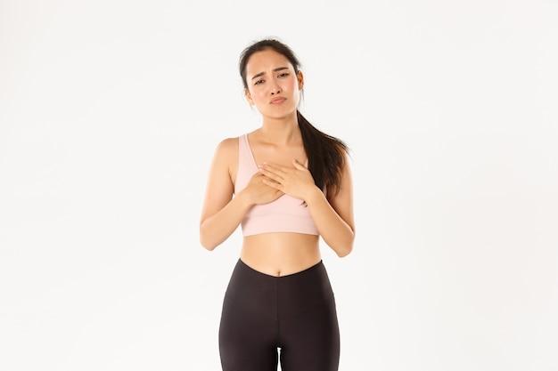 Мрачная жалующаяся азиатская фитнес-девушка, жаждущая чего-то, держащая руки на сердце и дутая ревнивая, чувствующая сожаление или расстроенную, белый фон