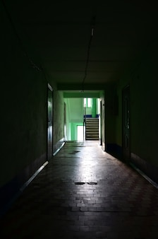 The gloomy corridor of a neglected public building.