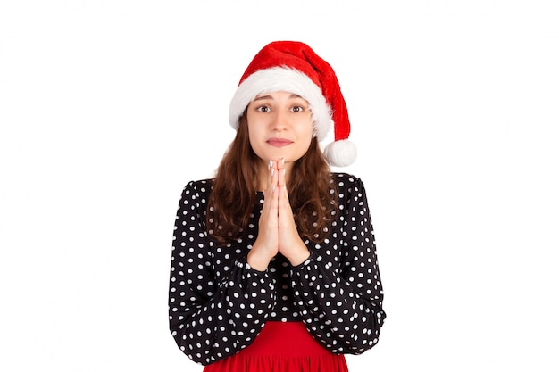 Gloomy cute and timid woman in dress holding hands in pray, asking for apology or help. emotional girl in santa claus christmas hat