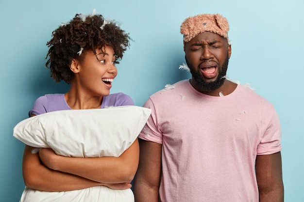Gloomy dark skinned guy wears eyemask, feels sad after loosing pillow fight, glad afro woman has feathers in head, looks away, stand closely over blue wall. morning routine and awakening