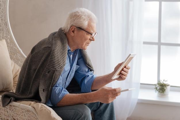 Мрачный подавленный мужчина смотрит на старую фотографию и вспоминает свое прошлое, сидя у окна
