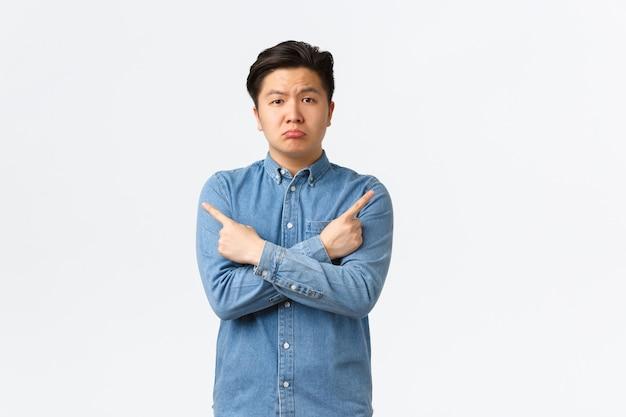 Мрачный разочарованный симпатичный азиатский парень дуется, что-то жалуется, с сожалением смотрит, как показывает пальцем в сторону, показывает левый и правый варианты, оба плохие, стоит на белом фоне
