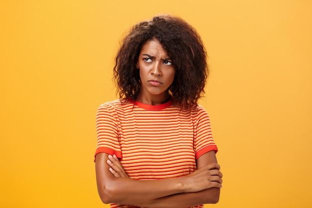 Мрачная недовольная и грустная афро-американская молодая женщина с вьющейся прической, скрестив руки на груди, в оскорблении.