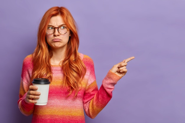 Gloomy displeased redhead woman wears spectacles and jumper drinks coffee to go and points away with sullen expression.