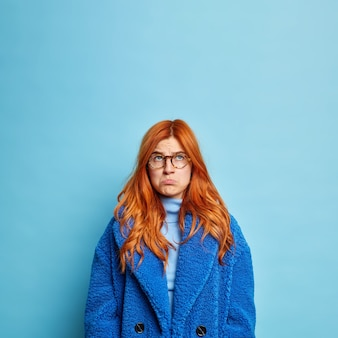 Gloomy displeased redhead young woman purses lips and looks sadly above stands discontent wears fur blue coat.
