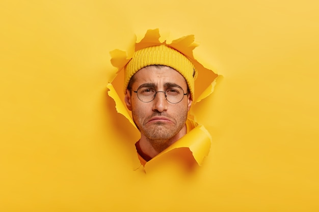 Gloomy dissatisfied caucasian man smirks face from negative emotions, has sad look, wears yellow hat