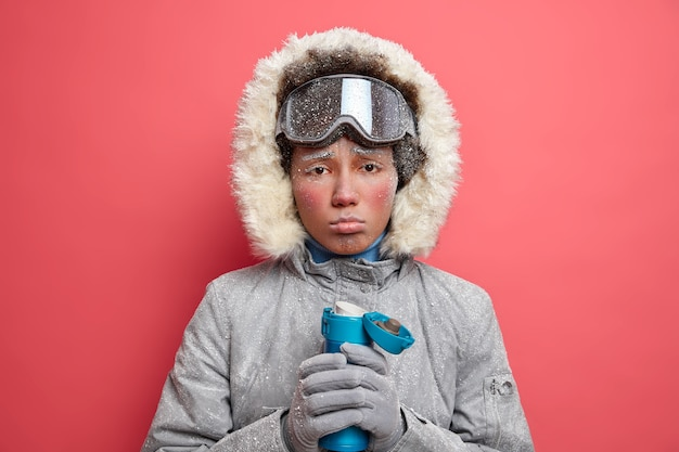 Gloomy frozen woman purses lips and looks upset feels tired after winter sport drinks hot beverage to warm herslef dressed in coat and gloves has ski touring.