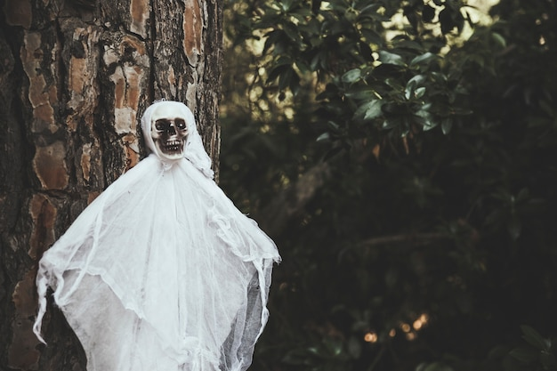 Gloomy ghost hanging on tree