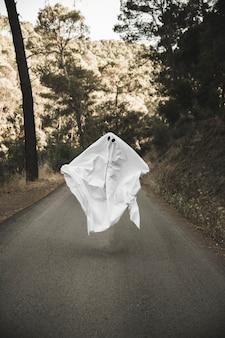 Gloomy ghost levitatingabove countryside route