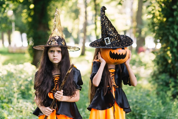 Gloomy girls in sorceress costumes in park