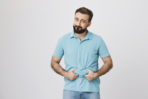 Gloomy guy need lose weight, showing fat belly