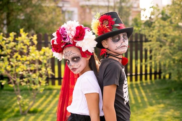 우울한 할로윈 소년과 소녀는 화창한 날 시골집에 가까이 서서 당신을 바라보고 있습니다.