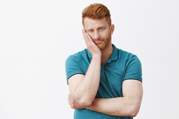 Gloomy indifferent redhead guy with bristle in green polo shirt, leaning face on palm and gazing aside with boredom