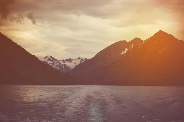 暗い黒い湖と背景に雪に覆われた山頂のある高い崖のある暗い風景。湖に沈む夕日、山の後ろに沈む太陽