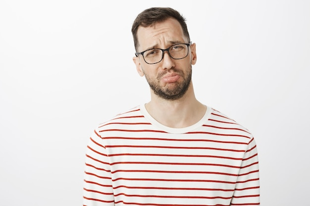 Gloomy man with beard in glasses, pouting and crying, complaining to friend about boyfriend who forgot about anniversary