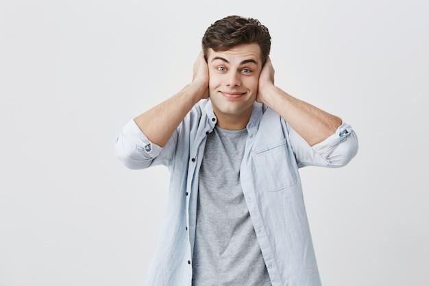Мрачный насмешливый молодой кавказский парень одет в голубую рубашку, делает лица, улыбается, закрывает уши ладонями, отказывается слушать чьи-то слова, позирует.