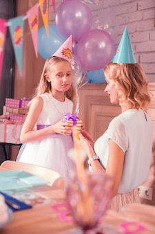 Gloomy mood. calm young woman sitting next to her daughter and the girl feeling gloomy at her birthday party