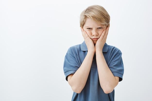 Хмурый обиженный симпатичный мальчик в синей футболке, хмурясь и недовольно глядя, сжимая щеки ладонями
