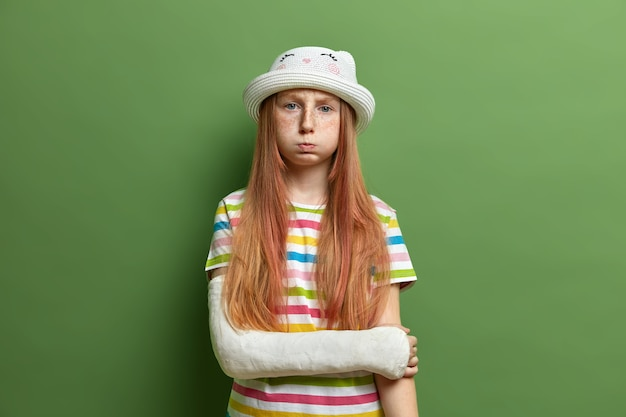 Gloomy offended girl blows cheeks, has displeased grimace after quarrel with mother, wears hat and striped t shirt, isolated over green wall. negative face expressions, bad mood concept