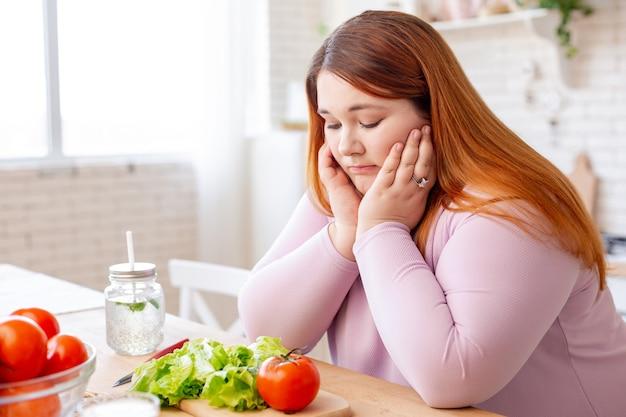 Мрачная пухлая женщина смотрит на овощи, не желая есть салат